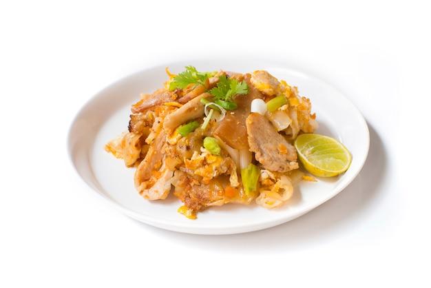 白い背景の白い皿に醤油と豚肉の平らな麺炒め