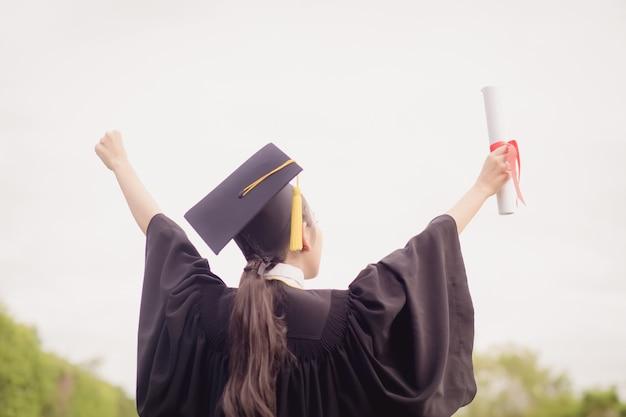 大学院生は彼女の手を上げ、彼女の手に証明書で祝う