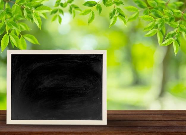 黒い木の木の竹のフレーム、概念の教育のための自然の背景に黒板