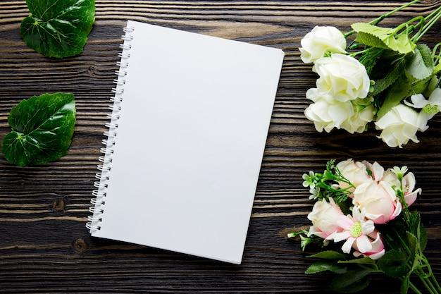 Букет из цветов и пустой дневник записной книжки на деревенском деревянный стол с копией пространства.