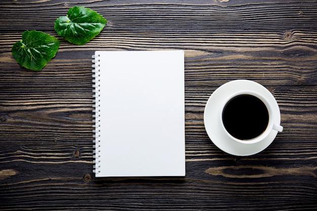 Букет из цветов и пустой дневник записной книжки и чашку кофе на деревенском деревянном столе.