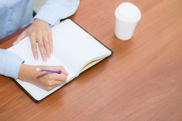 Крупным планом женщина рука, писать на ноутбук на деревянный стол.
