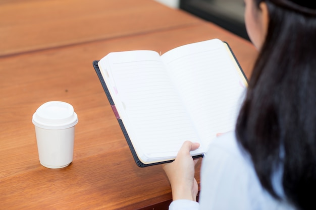 Макрофотография женщина рука, писать на ноутбуке на деревянный стол
