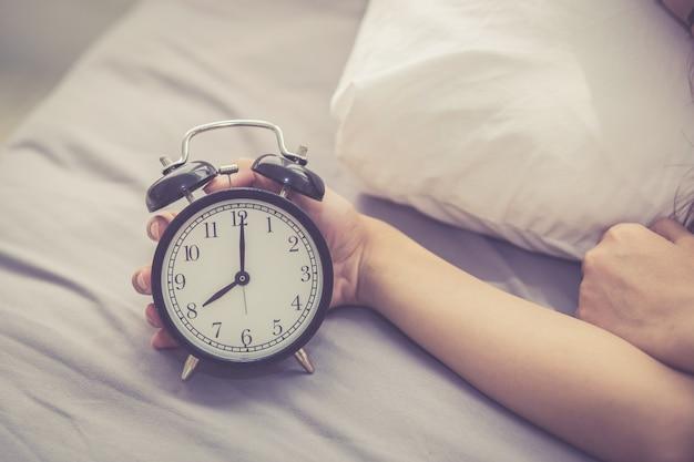 Макрофотография азии женщина выключить будильник в хорошее утро
