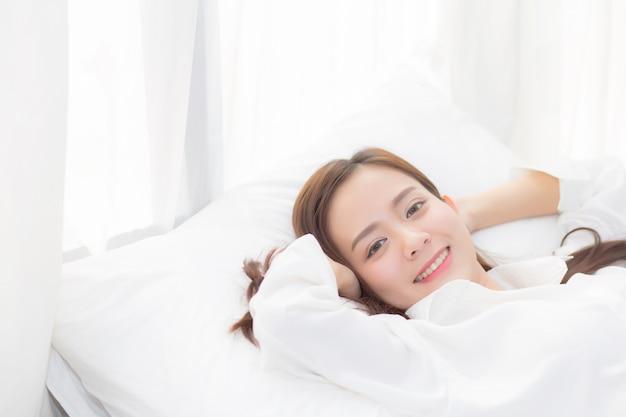 Красивая азиатская женщина спит лежа в постели.