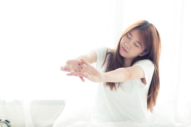 美しいアジアの女性がストレッチし、ベッドでリラックス