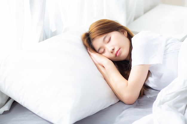 Портрет красивой азиатской молодой женщины спит лежа в постели