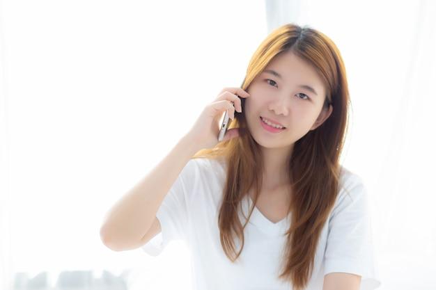 美しい若いアジアの女性が笑って座って、ベッドでリラックス