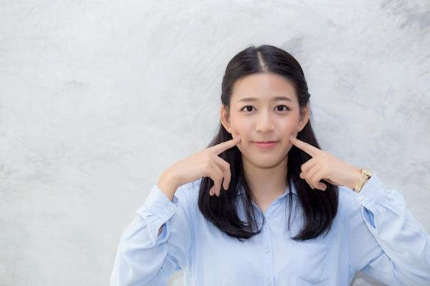 美しいアジアの女性の幸せ立っているタッチの頬の肖像