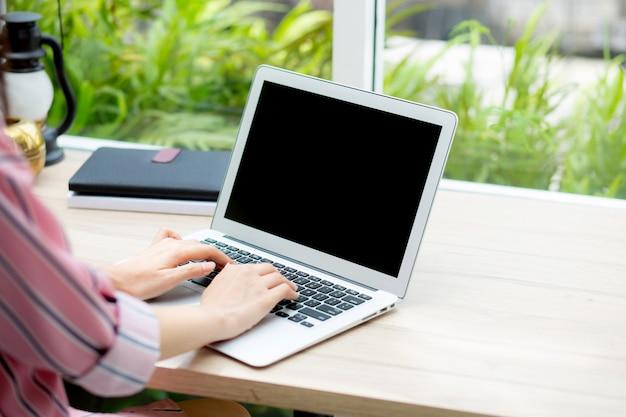 ラップトップコンピュータでオンラインで働く美しい女性