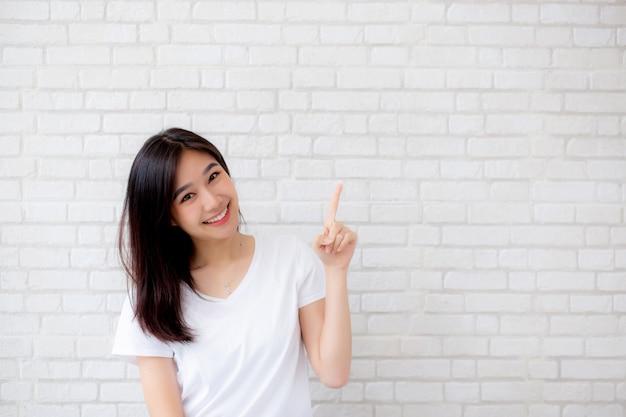 肖像画美しいアジアの女性の幸せ立っている指が何かを指す