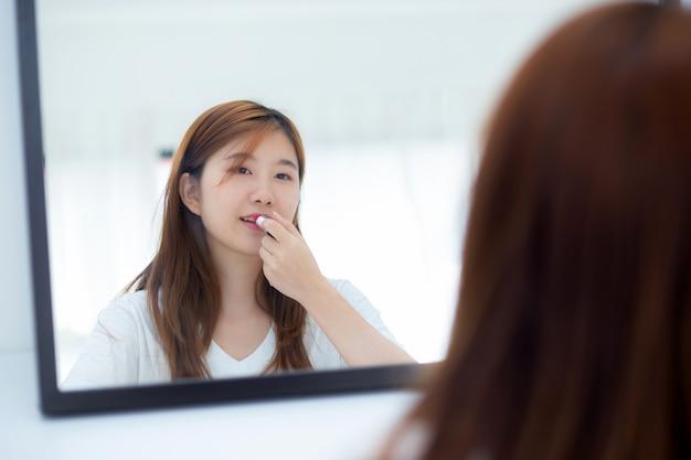 保持して化粧口紅を探して鏡で美しさの肖像画アジアの女性