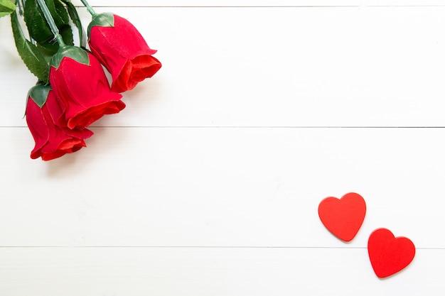 赤いバラの花とハートの形の木のプレゼントを木製のテーブル