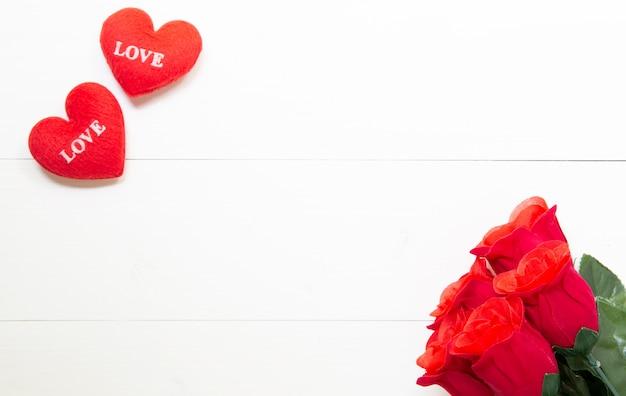 木製のテーブルに赤いバラの花とハートの形でプレゼントを贈る