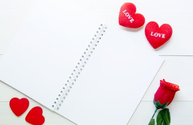 赤いバラの花とハートの形と木製のテーブル上のノートブックをプレゼント