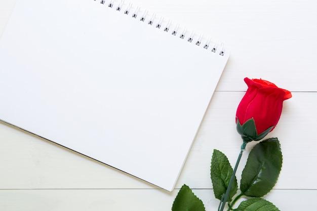 赤いバラの花と木製のテーブルの上のノートのプレゼントを贈る