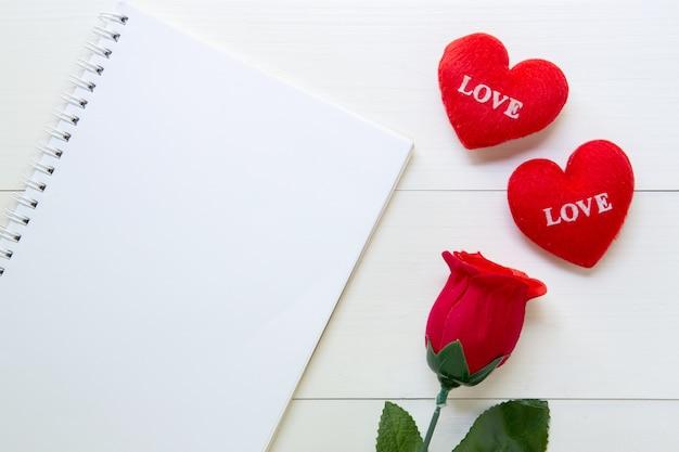 木製のテーブルにコピースペースを持つ現在の赤いバラの花とノートとハート