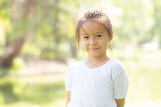 かわいいアジアの小さな女の子と子供の幸せと夏の公園で楽しいの肖像画顔