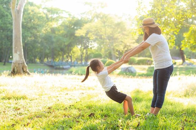 若いアジアの母と娘が公園で遊んで