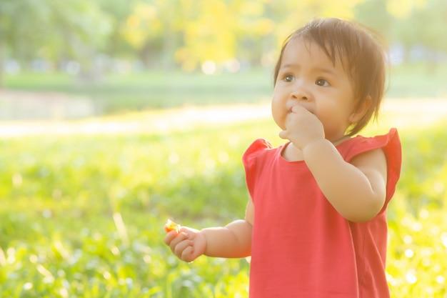 かわいいアジアの小さな女の子と子供の幸せと公園で楽しいの肖像画の顔