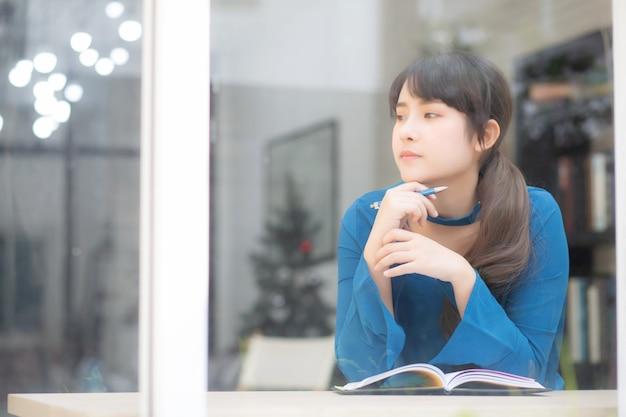 Идея красивого портрета молодого азиатского писателя женщины усмехаясь думая и сочинительство на тетради