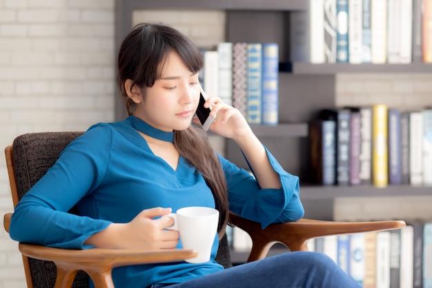 モバイルスマートフォンを使用して笑顔の美しい肖像若いアジア女性