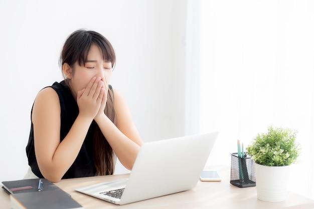 Красивейшая молодая независимая азиатская работа женщины скучала и утомляла на портативном компьютере