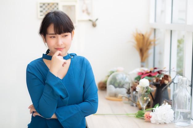 カフェに座って笑顔の美しい肖像若いアジア女性