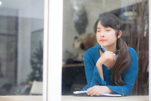 美しい肖像若いアジア女性作家の思考のアイデアを笑顔とノートに書く