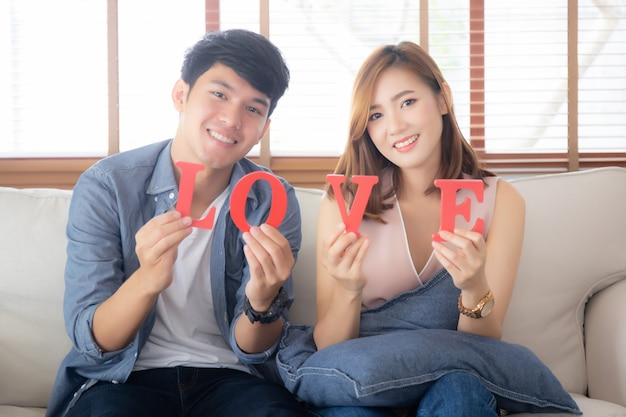 Пары красивого портрета молодые азиатские сидя на софе держа слово любят совместно