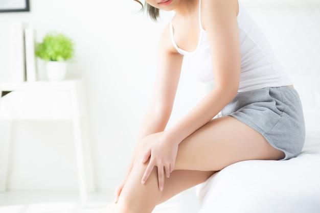 Красивая молодая азиатская женщина сидя на кровати поглаживая ноги с мягкой ровной кожей