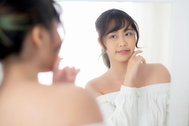 ミラーを見て笑顔の美しさの肖像若いアジア女性