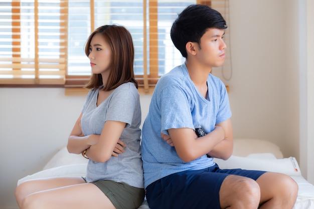 寝室のベッドで問題を抱えている若いアジアカップルの関係