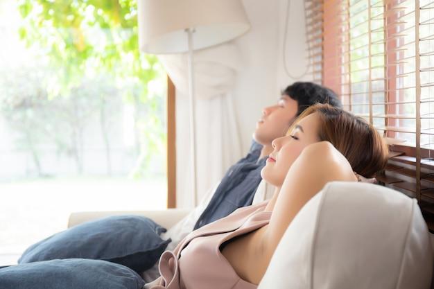 若いアジアカップルはソファで快適にリラックスします。