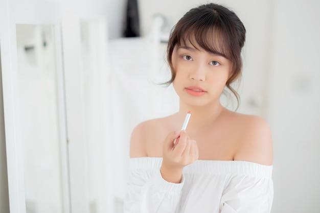 Женщина красивого портрета молодая азиатская смотря зеркало прикладывая губную помаду состава на комнате.
