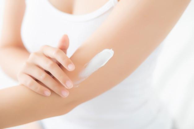 肌に日焼け止めクリームローションを適用するクローズアップ若いアジア女性