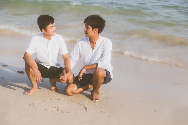 若いアジアのカップルのゲイが一緒にハートの形を描きます。