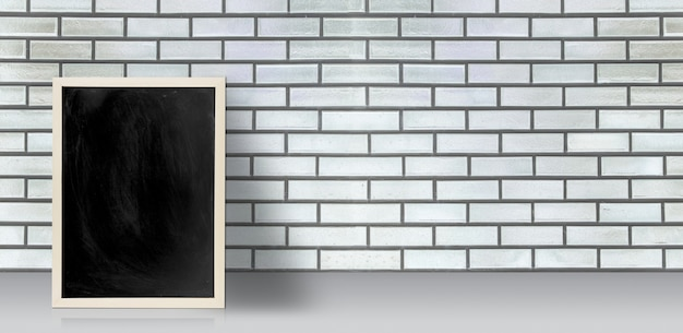 Пустая доске, доска на полу с белой кирпичной стеной с копией пространства