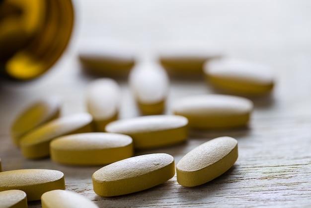 Таблетки витамина с выливают открытый контейнер