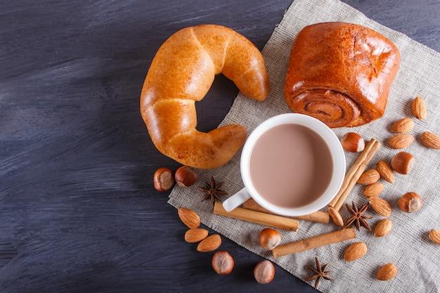ナッツ、パン、スパイス、黒い木製の背景にホットチョコレートのカップ。