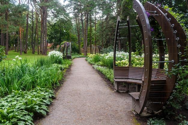 Лесопарк с большими деревьями и креативными скамейками и арками.