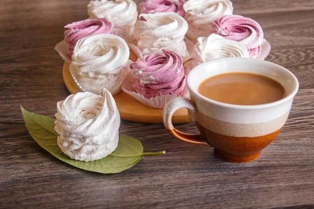 Розовые и белые зефиры (зефир) на круглой деревянной доске