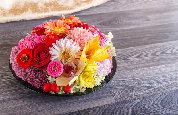 皿の上の秋の花のフラワーアレンジメント