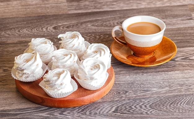 Белый зефир (зефир) на круглой деревянной доске с чашкой кофе