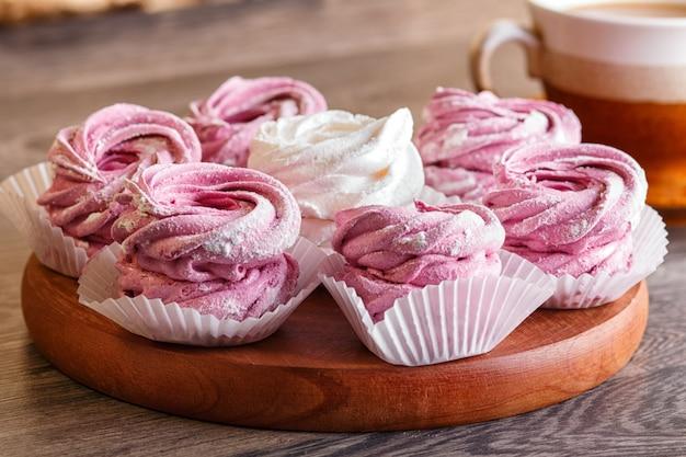 Розовые и белые зефиры (зефир) на круглой деревянной доске с чашкой кофе