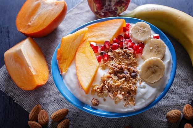 Синяя тарелка с греческим йогуртом, мюсли, хурмой, бананом, гранатом