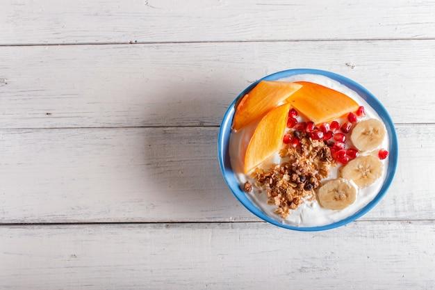 Синяя тарелка с греческим йогуртом, мюсли, хурмой, бананом, гранатом на белом фоне деревянные.