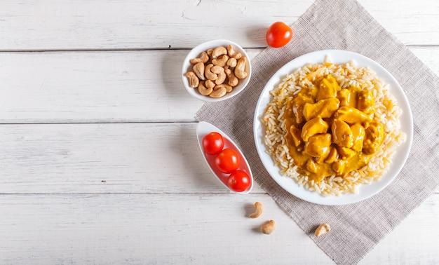 白い木製の背景にカシューナッツのチキンカレーソース添えご飯。