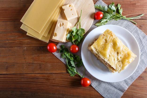 ひき肉と茶色の木製の背景にチーズのラザニア。