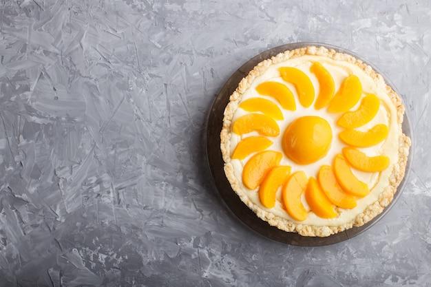 灰色のコンクリート背景に桃のチーズケーキ。